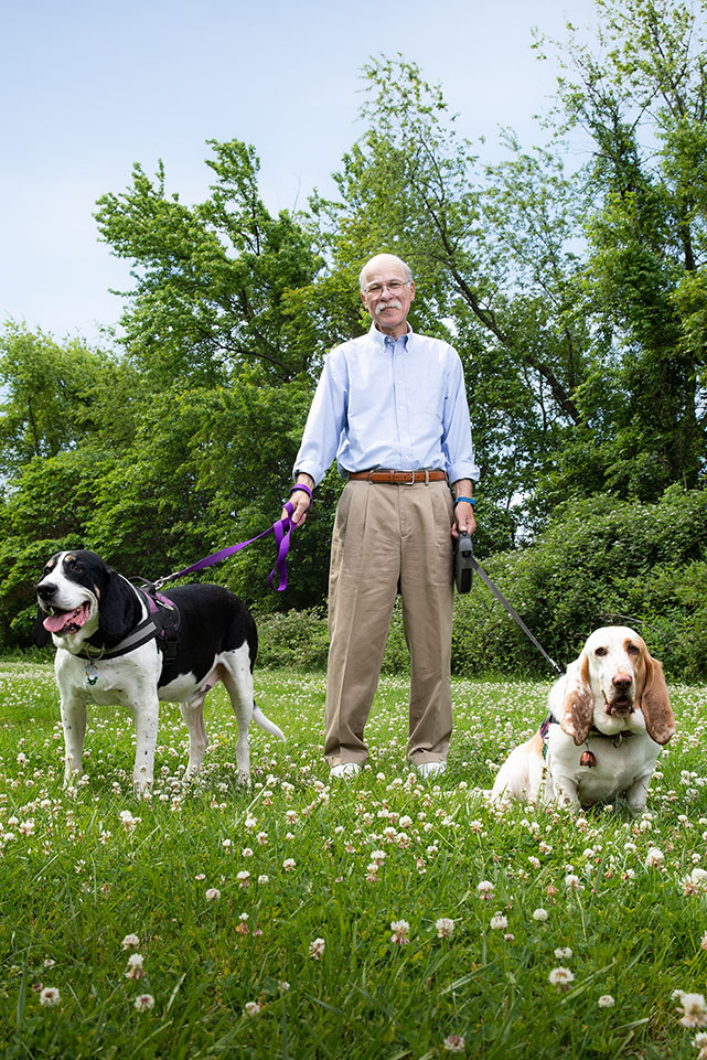 Alan standing with his two dogs.