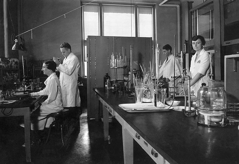 The lab of organic chemist Gerrit Toennies in the Wanamaker building on the Lankenau Hospital campus in 1935. Shown left to right are Peg Elliott, Toennies, Theodore Lavine, and Mary Adelia Bennett.