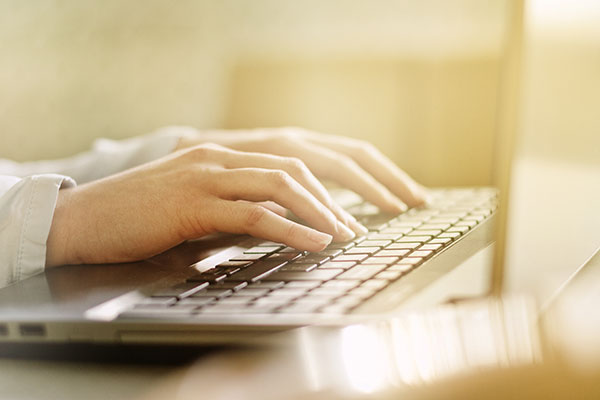 Photograph of a woman typing on a laptop